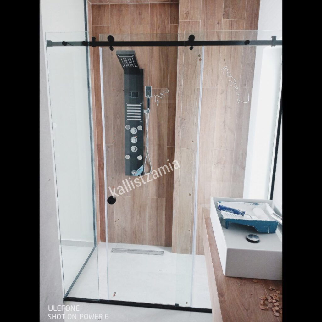Καμπίνα μπάνιου με οδηγό αλουμινίου,μαύρα εξαρτήματα,συρόμενη πόρτα,διάφανοι υαλοπίνακες.ΚΑΛΛΗΣ ΤΖΑΜΙΑ